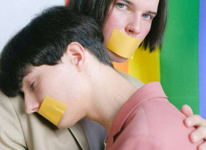 two-men-with-adhesive-tape-over-their-mouth-hugging-4611699